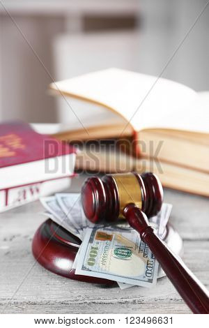 Gavel with books and money on wooden table closeup