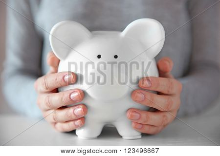 Woman holding in hands white piggy bank at the table