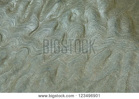 abstract curved lines on wet sand created by the ocean.