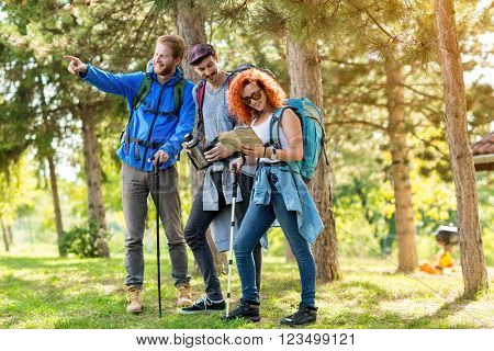 Hiker girl with male fellows look at map in forest
