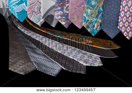 neckties hanging vertically and laid flat against black background