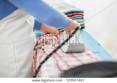 Close up of housewifeâ??s hand pressing shirts
