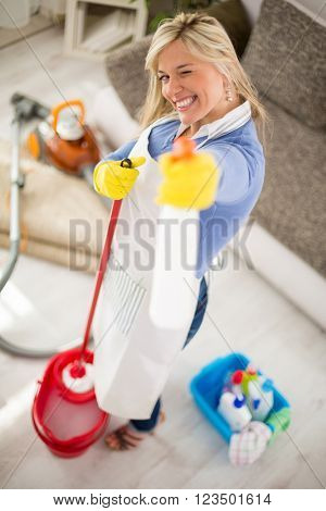 Cheerful housemaid with products for cleaning house in hands make joke