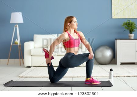 Young sportswoman doing exercises on a mat at home