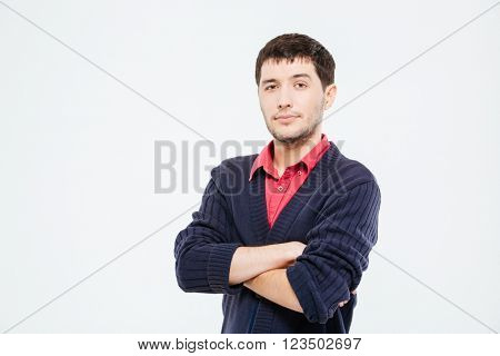 Handsome young man standing with arms folded isolated on a white background