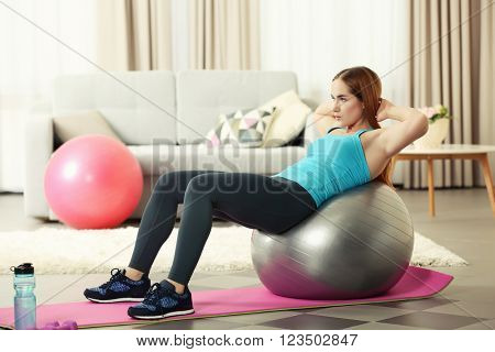 Young sportswoman doing exercises with ball on a mat at home