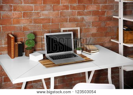 Workplace with laptop, table and bookcase on brick wall background