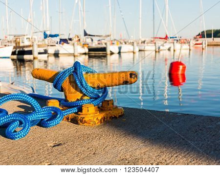 Yellow mooring bollard with blue rope in marina yachts in the background