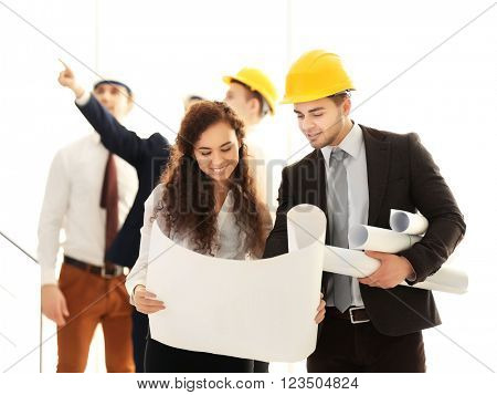 Few engineers with blueprint in office