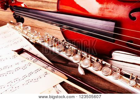 Flute and violin with musical notes on wooden table close up