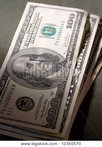 close-up view of pile of US dollars banknotes with light and shadow