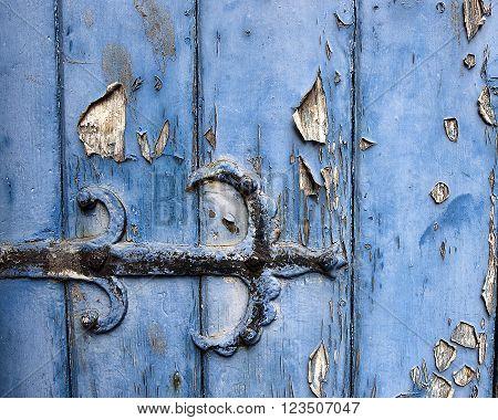 Detail of hinge on old door with peeling paint