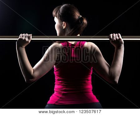 Brunette woman with crossbar on black background