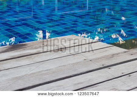closeup swimming pool with stair and wooden deck.