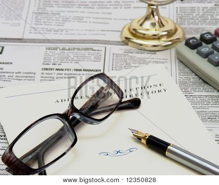 glasses, pen and telephone directory on the newspaper