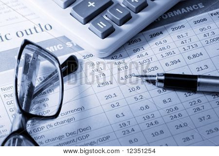 "pen, calculator and glasses on the newspaper with table ""Economic structure and performance"" made with blue tones"