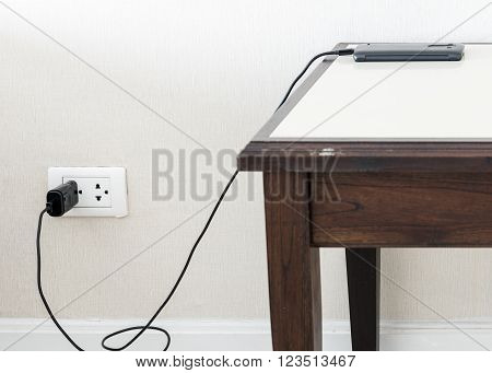 Black smart phone is charging with wall outlet on the wooden tableSelect focus