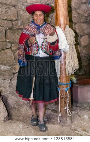 Ollantaytambo, Peru - Circa June 2015: Woman In Traditional Peruvian Clothes Makes Yarn From Alpaca