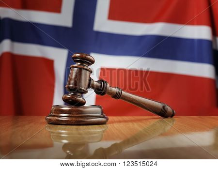 Mahogany wooden gavel on glossy wooden table, flag of Norway in the background.