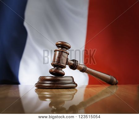 Mahogany wooden gavel on glossy wooden table, flag of France in the background.
