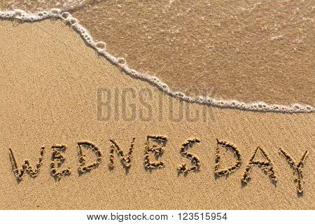 Week series - WEDNESDAY - written on a sandy beach with the soft wave at sunny day.