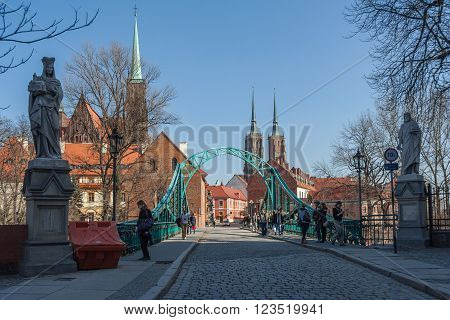 Wroclaw, Poland - Circa March 2012: Most Tumski Bridge, Sculptures And Towers Of Gothic Cathedral Of