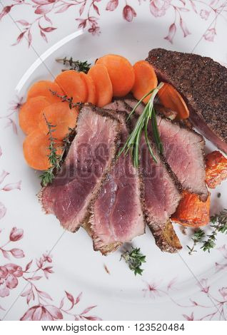 Medium rare beef steak with fresh carrot, rosemary and thyme