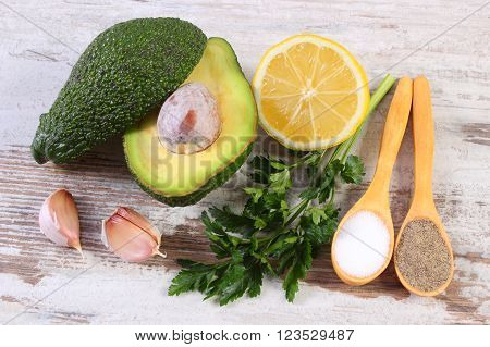 Avocado with ingredients and spices to avocado paste or guacamole, garlic, lemon, parsley, concept of healthy food, nutrition and omega fatty acids