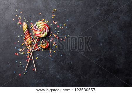 Colorful candies lollipops over stone background. Top view with copy space