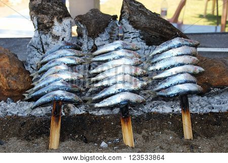 Sardines cooking on a log fire in a boat along the promenade Benalmadena Costa del Sol Malaga Province Andalusia Spain Western Europe.