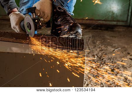 Worker working of a grinding machine with a lot of sparks