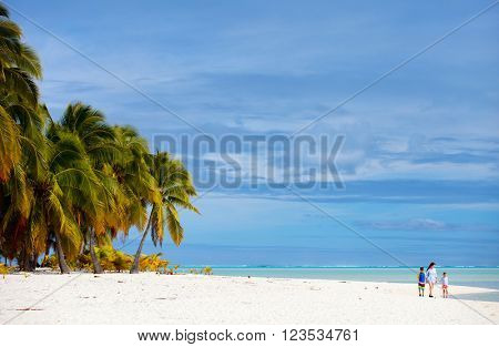 Mother and kids family at tropical beach on Aitutaki island, Cook Islands, South Pacific