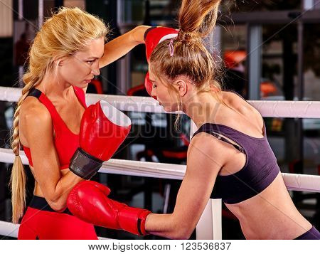 Two women boxer wearing red  gloves to box in ring. Martial arts concept.