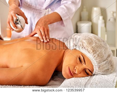 Woman middle-aged take back massage in spa salon with young beautician. Care of health.
