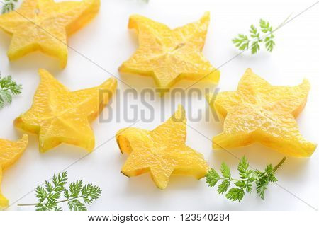 slice of starfruit and leaves on white background