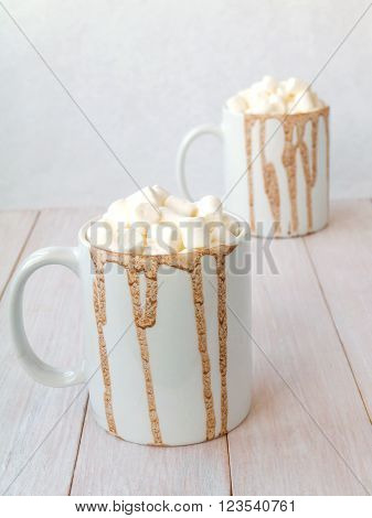 Hot cocoa with marshmallow topping in white mugs with chocolate drops