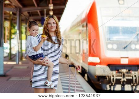 Yound woman and little girl, lovely daughter, on a railway station. Kid and woman waiting for train and happy about a journey. People, travel, family, lifestyle concept