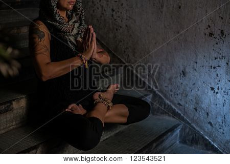Cropped image of female yogi  meditating on the steps