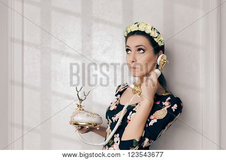 Undecided Retro Woman With Vintage Phone - Young woman talking on a classic embellished telephone