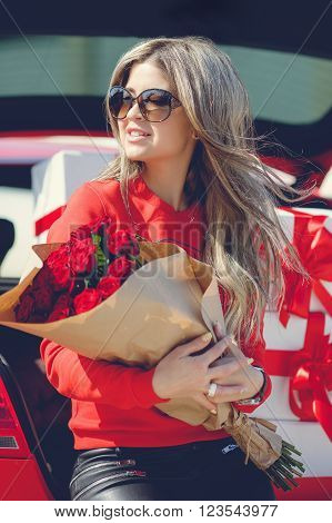 The young woman, the blonde with a thick long hair, in sun glasses, a red t-shirt and black leather trousers, with a big bouquet of scarlet roses poses near the red car loaded by gift boxes