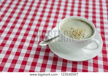 Black coffee with rich crema in a white porcelain cup on a background of red and white checkered cloth