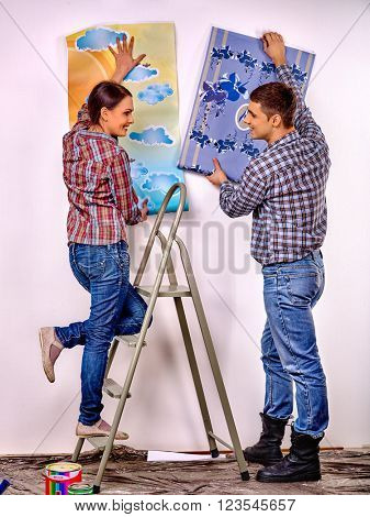 Happy family glues wallpaper on  stepladder at home.