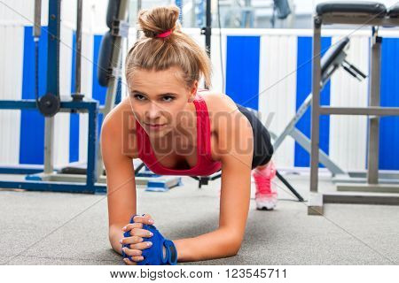 Young strong woman doing some push ups in sport gym.