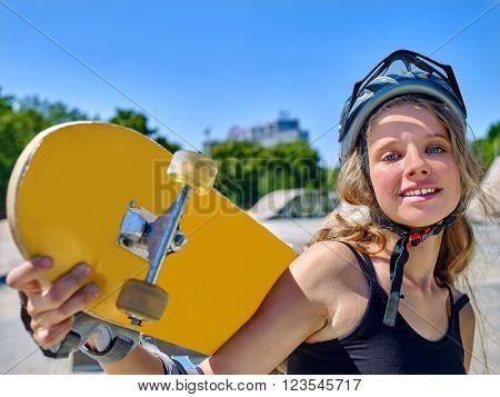 Teen skateboarding keeps her skateboard  on her back outdoor. Skateboard girl style.