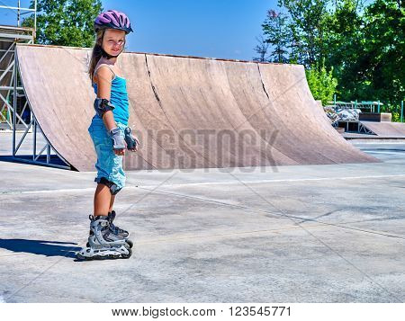 Girl wearing protection riding on roller skates in skatepark.