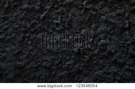 Rough wall covered with dark gray stucco