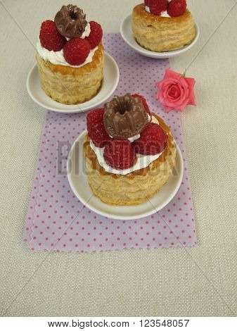 Sweet puff pastry cakes filled with raspberry, whipped cream and chocolate