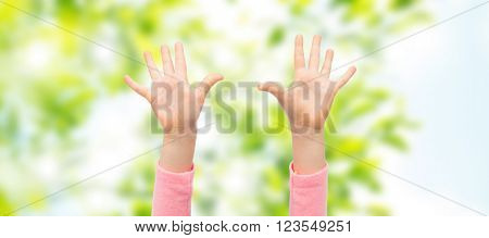 people, childhood, gesture and body parts concept - close up of little child hands raised up over green natural background