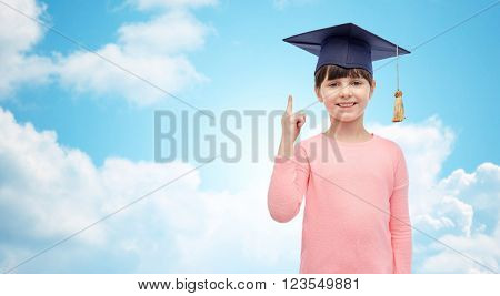 childhood, school, education, learning and people concept - happy girl with in bachelor hat or mortarboard over blue sky and clouds background