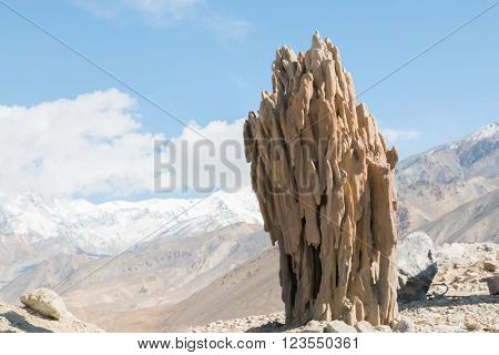 Stalagmite like geological formation outside in front of a mountain landscape on a sunny day
